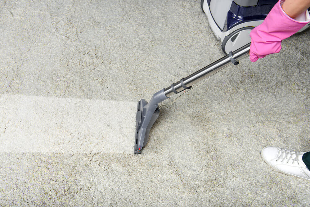 a carpet shampooer worker cleaning a white carpet whilst wearing pink gloves