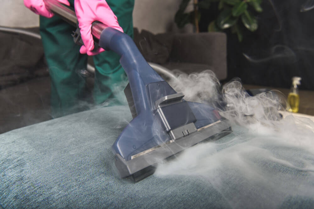 close up of a steam upholstery cleaner vacuum with steam coming out everywhere